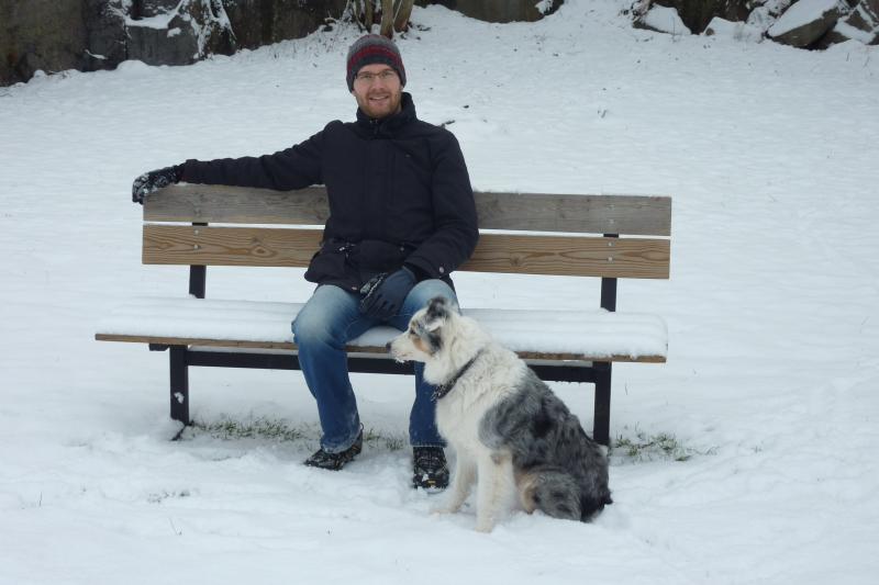 Marcel sitzt auf einer schneebedeckten Bank